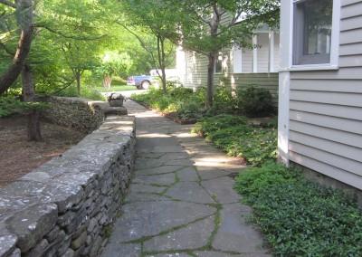 Stone wall, natural stone sidewalk with perennial border