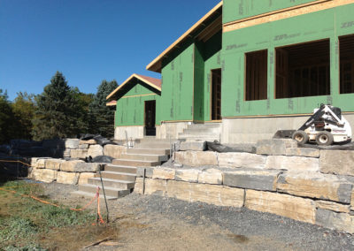 Integration of natural stone steps and retaining walls to mitigate 8′ of fill with tight site restrictions